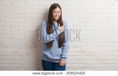 Young Chinise woman over white brick wall cheerful with a smile of face pointing with hand and finger up to the side with happy and natural expression on face looking at the camera.