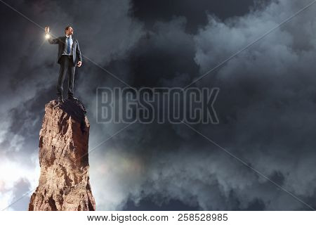 Businessman With Glowing Lamp Standing On Mountain Top. Cloudy Sky Background. Innovation And Leader