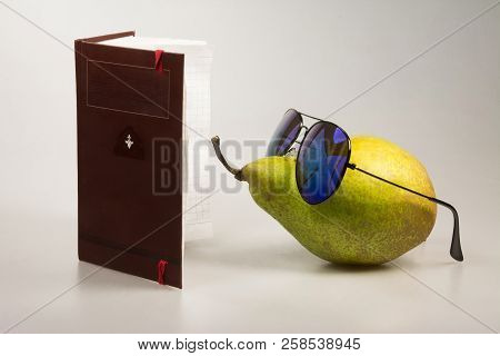 Green Pear In Dark Glasses And A Notebook. Humorous Still Life