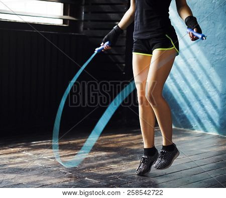Young Serious Female Boxer In Wrapped Hands Warming Up, Jumping On Skipping Rope In Gym. Fit Woman P