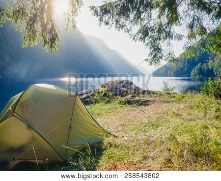 Sunlit camping tent at scenic campsite on a lake shore with mountain range in background - wild camping in Norway
