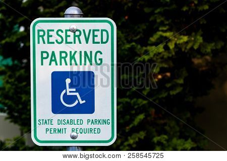 Reserved Handicapped Permit Parking Only Sign In Front Of Green Bushes