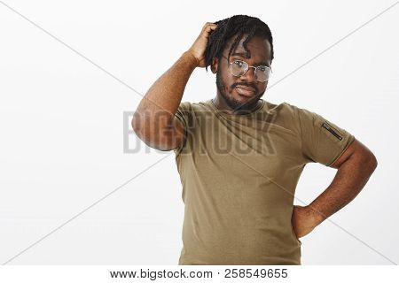 Indoor Shot Of Unsure Handsome African American In Glasses, Holding Hand On Hip And Scratching Head,