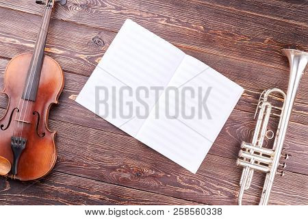 Old Violin, Trumpet And Musical Notes. Symphonic Music Instruments On Wooden Background. Orchestra M
