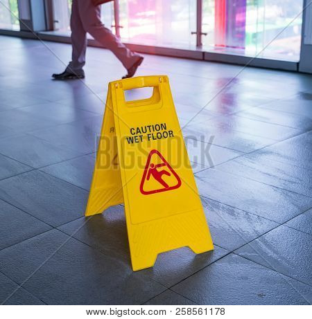 Yellow Caution wet floor sign on wet floor