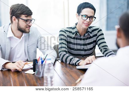 Two Young Employers Having An Interview With Emloyee At The Table At Office