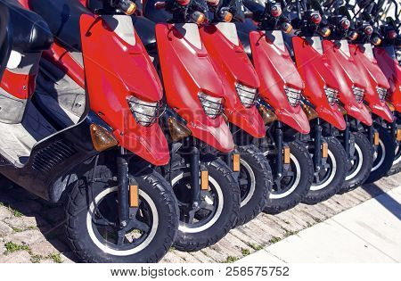 Red Scooters Or Motorcycles For Sale Or Hire Standing In Row With Wheels And Lights Sunny Day Outdoo