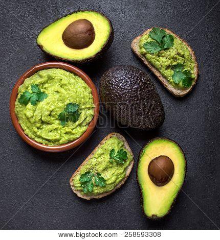 Mexican Dip Sauce Guacamole With Avocado  In A Clay Bowl  On Black Background. Avocado Spread. Top V