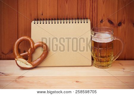 Beer Mug, Empty Notebook And Pretzel On Wooden Table. View With Copy Space.
