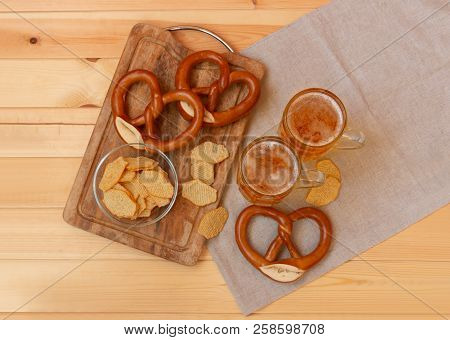 Beer Mugs, Potato Chips And Pretzels On Wooden Table. Top View.