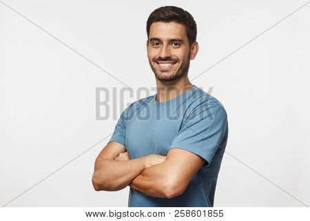 Portrait Of Attractive Young Sporty Man In Blue T-shirt Standing With Crossed Arms Isolated On Gray
