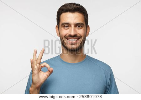 Young Smiling Man Having Happy Look, Gesturing, Showing Ok Sign Or Showing Okay Gesture With His Fin