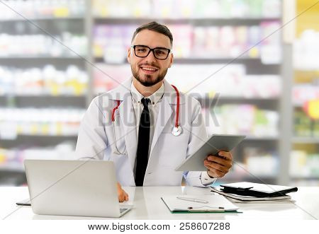 Pharmacist Using Tablet Computer At Pharmacy.