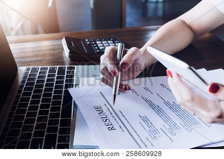 Woman Holding Pen Over Resume Application With Smart Phone And Using Computer Laptop To Job Search O
