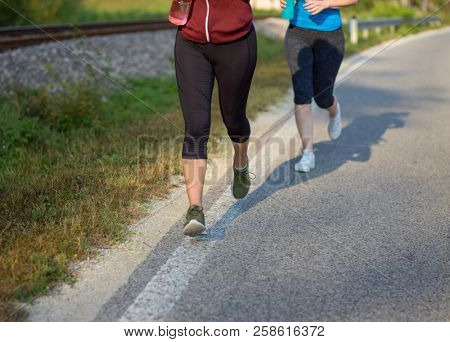 two young women enjoying in a healthy lifestyle while jogging along a country road, exercise and fitness concept