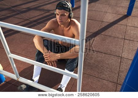Athletic Caucasian Muscular Young Male Relaxing On Sports Ground Outdoors. Handsome Athlete Man Look