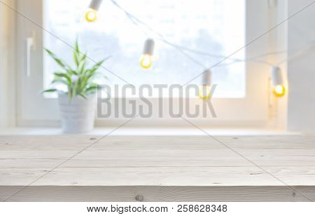 Wooden Empty Board Over Blurred Holiday Window With Garland Lights