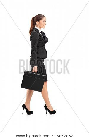 Full length portrait of a businesswoman walking with a briefcase in her hand isolated against white background