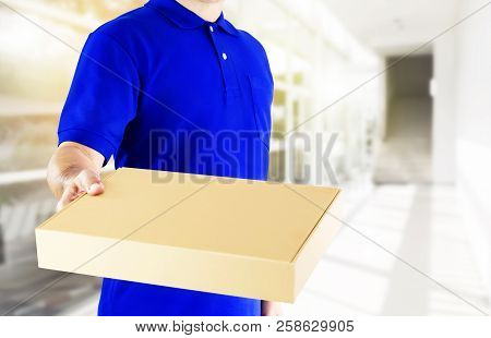 Delivery Man In Blue Uniform And Holding Paper Box With Delivering Package On Office Background. Con