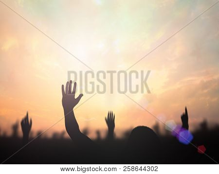Worship Concept: Silhouette Christian People Hand Rising Over Blurred Cross On Spiritual Light Backg