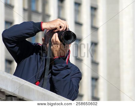 Person With A Slr Camera In His Hands. Man Photographing In Sunny Day Outdoor On City Background, Co