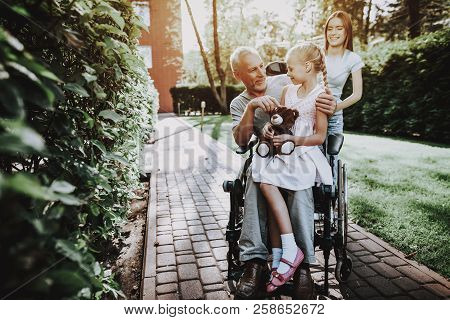 poster of Aged Man with Girl. Girl with Bear on Stroller. Businessman in Stroller with Happy Child. Smile all Family. Rehabilitation With Wheelchair. Caregiver with Old Man and Child. Together Happy Family.