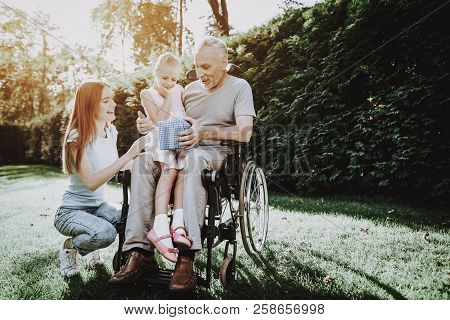 Happy Family On Nature With Child. Family And Caregiver. Child And Old Man. Health Girl With Aged. H