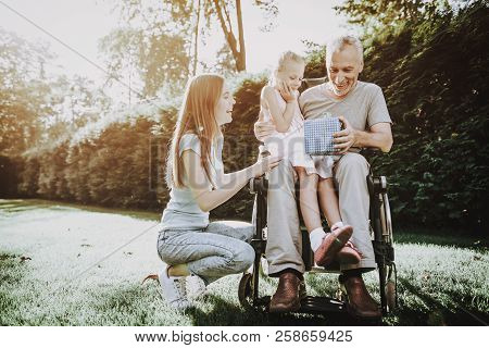 Heppy Old Man With Family. Gift For Old Man On Wheelchair. Woman And Girl Care About Aged. Senior Nu