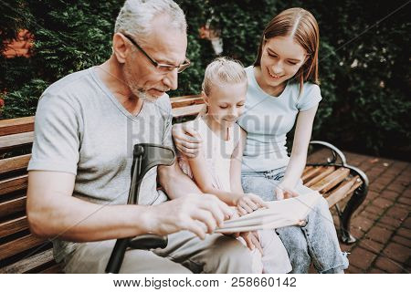 Book On Bench With Old Man. Businessman With Girls Reed Book In Bench. Family Spend Time Toggether.
