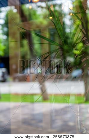 .close-up Of A Window With A Reflection Of The Street And A Cafe Outside The Window