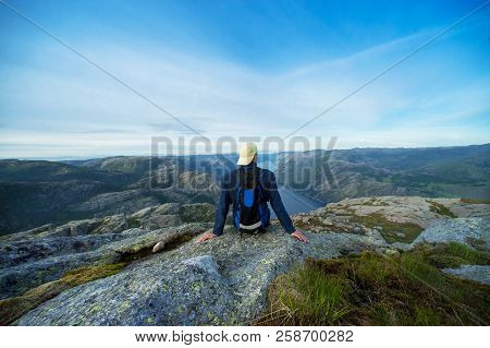 Guy Sitting On A Rock With A View Of Preikestolen, Lysefjorden  In The Background Of Roland County O