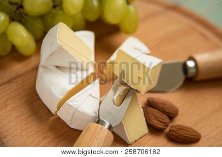 Cheese Camembert With Raspberries And Nuts, Melange On A Blue Background