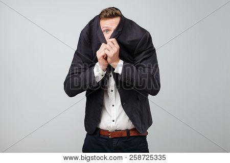 Afraid Young Business Man Hides His Face From Risky Business In Suit