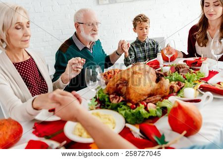 Happy Family Holding Hands And Praying At Served Table With Turkey Before Holiday Dinner On Thanksgi