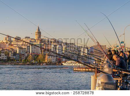 Istanbul, Turkey - April 25, 2017: Local Citizens Fishing At Golden Horn On Galata Bridge Before Sun