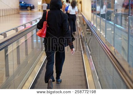 Woman At Horizontal Escalator Covered. Moving Walkway, Moving Sidewalk, Moving Pavement, Autopedesca