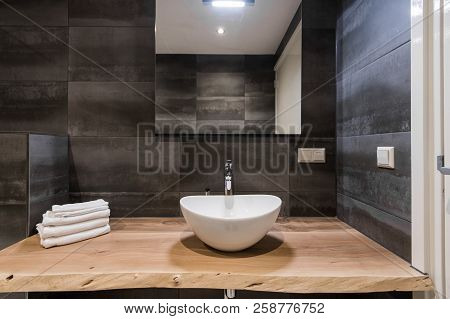 Modern Interior Of The Bathroom. The Washbasin Is Made Of White Massive Shell On The Table Of Wood.