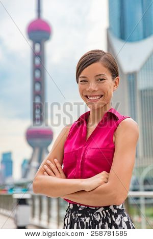 Happy Asian business woman portrait in Shanghai, China Pudong financial district and tower. Proud confident young successful corporate executive or professional Chinese multiracial businesswoman.