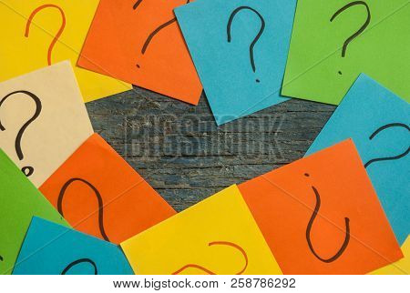 Too many questions on wooden background. Pile of colorful paper notes with question marks. top view.