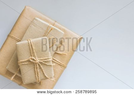 Stacked Gift Boxes Wrapped In Brown Craft Paper Tied With Twine Various Sizes. White Background Top