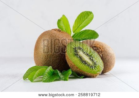 Ripe Fleshy Green Kiwi With Juicy Slice, Young Leaves On Soft Light White Table, Closeup. Tropical F