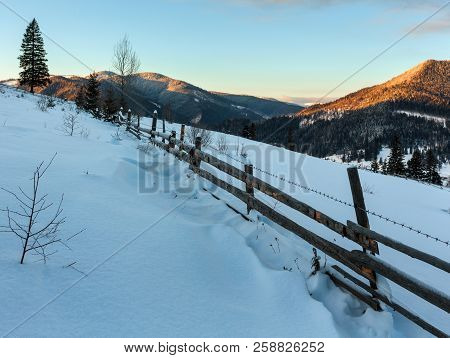 Sunrise Morning Winter Mountain Village Outskirts. View From Rural Snow Covered Path On Hill Slope,