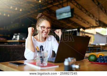 Portrait Of Happy Young Business Woman Celebrating Success With Arms Up In Front Of Laptop. Mixed Ra
