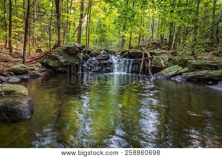 Apshawa Falls flows gently over tiered rocks surrounded in lush green forest; nature preserve in the NJ Highlands poster