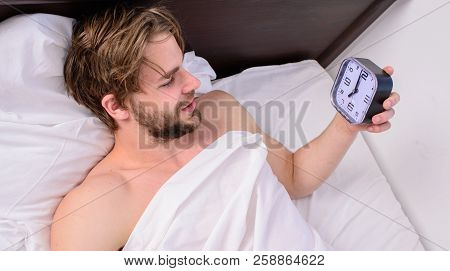 Stick sleep schedule same bedtime and wake up time. Sleep regime habits concept. Man sleepy drowsy unshaven bearded face covered with blanket having rest. Man unshaven lay awake bed hold alarm clock poster