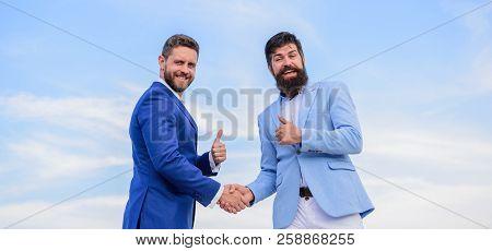 Business Partner Confirming Deal Transaction. Men Formal Suits Shaking Hands Blue Sky Background. En