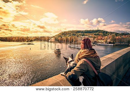 Young Women Tourist With A Puppy Dog And A Backpack Looking At The Tourist Boat And Swans Sailing On