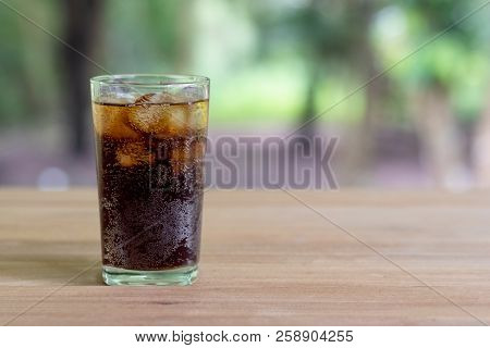 Refreshing Black Soda Soft Drinks Or Cola With Ice In A Clear Tall Glass With Nature Background.