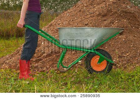 Worker with a wheelbarrow near gravel hill