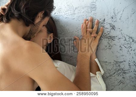 Close Up Of Passionate Lovers Holding Hands Kissing Near Wall